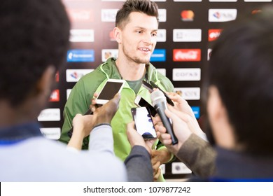 Portrait of handsome young sportsman giving interview to group of journalists during press conference