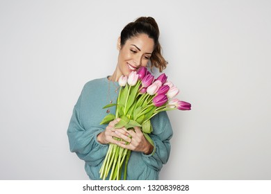 Portrait of a handsome young woman holding colored tulips bouquet isolated over gray background.