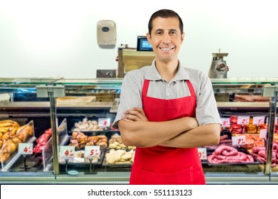 portrait of handsomemale butcher with arms crossed and smiling at the butchery