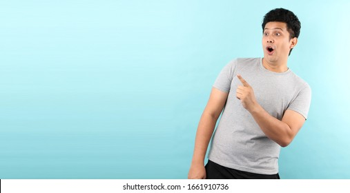 Portrait of handsome,Shock and surprise face of asian man Pointing finger on empty space isolated on blue background in studio With copy space.