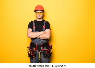 Portrait of handyman with tools belt isolated on yellow background