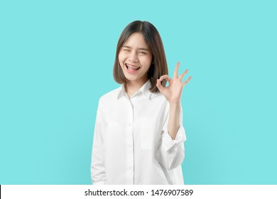 Portrait happily Asian woman shows ok sign and braces smiling witch looking at the camera on blue background, Cheerful girl gestures studio.