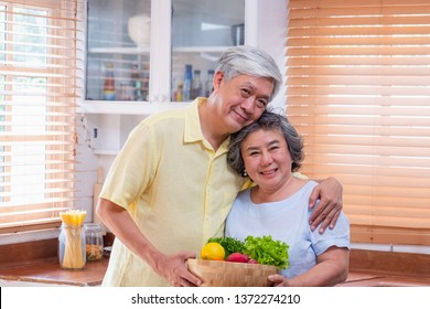 Portrait happiness asian senior couple  at kitchen with a bowl of fresh salad and looking at camera,aging at home conept.
