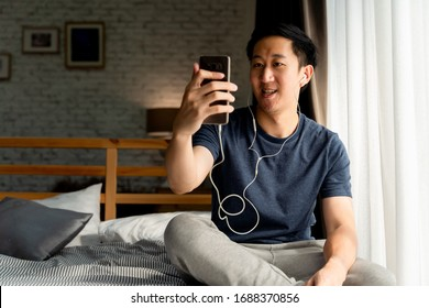 Portrait of happy 30s aged Asian man in casual clothing making facetime video calling with smartphone at home. He's waving at people on phone screen. Using conferencing meeting online app concept