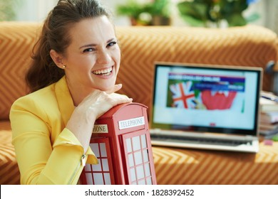 Portrait of happy 40 years old housewife in jeans and yellow jacket with red english telephone booth learning English language online on a laptop in the modern living room in sunny day.
