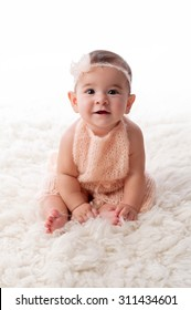 A portrait of a happy, 6 month old baby girl wearing a peach colored, knitted mohair romper. She is sitting on a cream colored sheepskin rug.