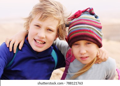 Portrait of happy 7 years old girl with her autistic 10 years old brother outdoors