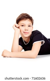 Portrait of a happy 9 year boy lying on a floor. Isolated over white background.