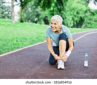 Portrait einer glücklich aktiven, schönen Seniorin, die nach dem Training im Freien auf ihrem Laufschuh ein Fixierschiff aufstellt