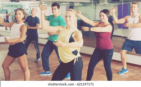 Portrait of happy active men and ladies dancing zumba at lesson