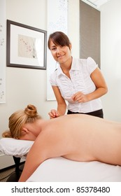 Portrait of a happy acupuncturist in her clinic with a female patient