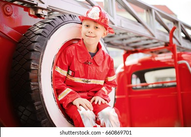 Portrait of Happy Adorable Child Boy with Fireman Hat Playing Outside siting in spare wheel of old shiny vintage red fire truck. Dreaming of future profession. Fire safety, Life Protection lessons