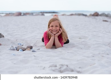 Portrait happy adorable little girl in neoprene swimsuits laying on the beach on white sand on Baltic sea