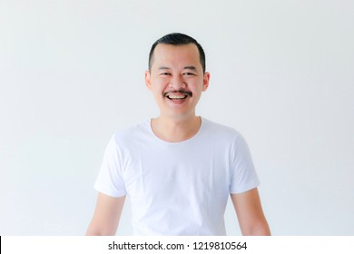 Portrait of happy adult asian man smiling or laughing and looking at camera isolated in bright background.