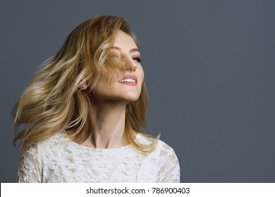 Portrait of a happy adult blonde woman spinning her head, grey background, copy space