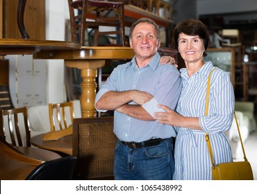 Portrait of happy adult woman with her husband who are satisfied of buying furniture in antique store