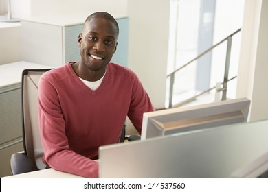 Portrait of happy African American businessman sitting at computer desk