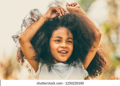 Portrait of happy African American child playing in outdoors park. Freedom and children health concept.