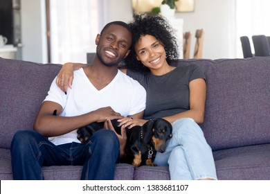 Portrait of happy African American couple hug sitting on couch with cute dog, smiling black husband and wife pose with dackel, relaxing together on sofa, young family with pet rest in own living room