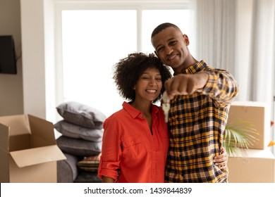 Portrait of happy African american couple holding new house keys in living room at home