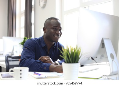 Portrait of a happy African American entrepreneur displaying computer in office.