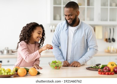 Portrait of happy african american father and little daughter cooking vegetable salad at modern kitchen, adding fresh tomato to bowl laughing together while making healthy lunch or breakfast at home