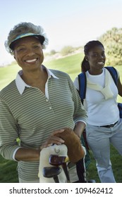 Portrait of happy African American female golfer with person in background