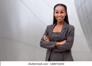 Portrait of a happy African American female company leader, CEO, boss, executive, standing in front of company building, copy space