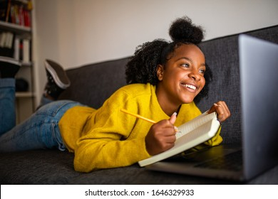 Portrait of happy african american girl student looking at laptop computer screen at home