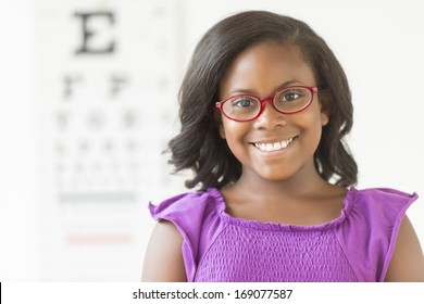 Portrait of happy African American girl wearing glasses against eye chart in clinic