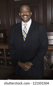 Portrait of a happy African American lawyer standing in the courtroom