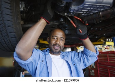 Portrait of a happy African American male mechanic repairing a lifted car In Garage