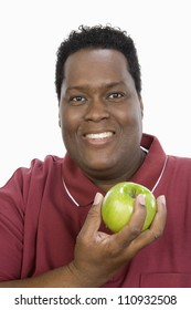 Portrait of happy African American man with an apple isolated over white background