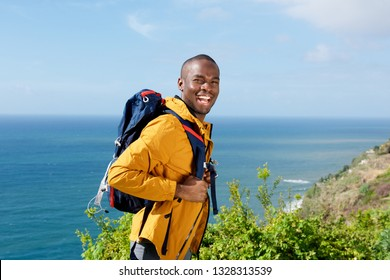 Portrait of happy african american man with walking backpack outdoors