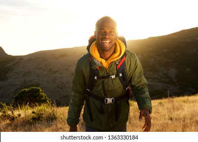 Portrait of happy african american man walking in with backpack in mountains and sunset in background