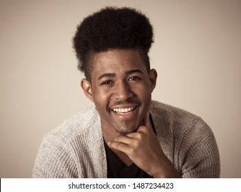 Portrait of happy african american man having fun and joy. Teenager smiling at the camera and looking to something that makes him laugh. In Human emotions facial expressions and youth happiness.