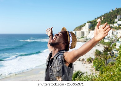 Portrait of a happy african american man with arms outstretched by the beach