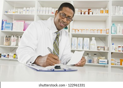 Portrait of a happy African American pharmacist writing prescription at workplace