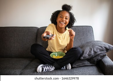 Portrait happy african american teenage girl sitting on sofa pointing tv remote control