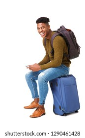 Portrait of happy african american travel man sitting on suitcase with mobile phone against isolated white background