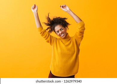 Portrait of happy african american woman with afro hairstyle rejoicing and dancing isolated over yellow background
