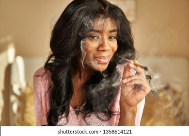 portrait of happy african american woman smoking pre-roll marijuana joint