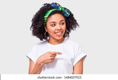 Portrait of happy African American young woman dressed in white t shirt and green trendy headband, indicates aside with forefinger to blank copy space, isolated over white wall.