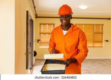 portrait of happy african builder holding paint roller and paint