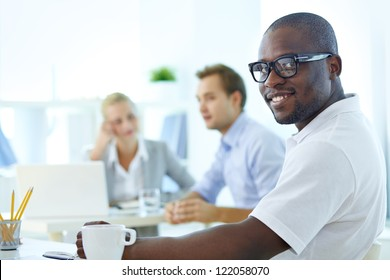 Portrait of happy African guy looking at camera in working environment