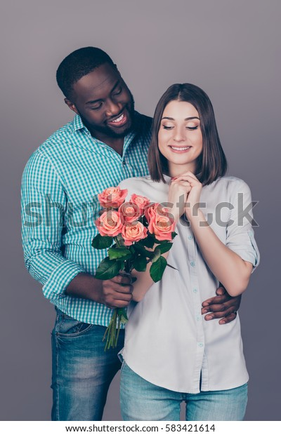 Portrait of happy african man giving bouquet of roses to his girlfriend