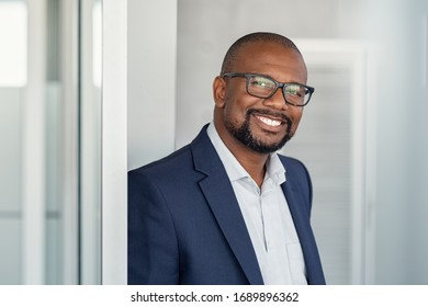 Portrait of happy african man wearing spectacles and looking at camera. Successful black businessman with beard feeling confident at work. Portrait of mature business man in formalwear smiling.