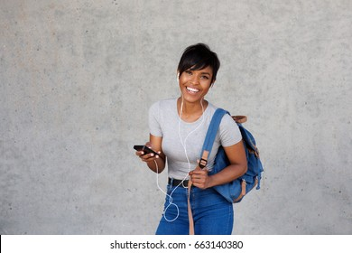 Portrait of happy african woman with bag listening music on mobile against gray wall