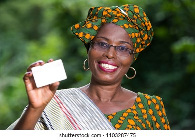portrait of happy african woman in traditional clothes standing in nature showing a credit card,