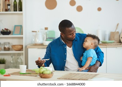 Portrait of happy African-American dad feeding cute little boy white sitting at kitchen table , copy space